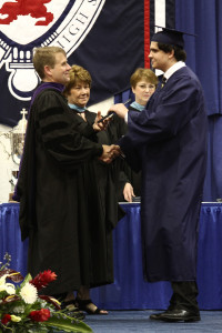 Anthony Zanocco receives his diploma from Fr. Corey Brost and Mrs. Eileen Manno, principal
