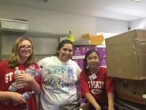 Pre-Associate Deborah Perez, center, helps lead teens at the food pantry