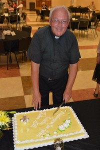 Fr. Bill Haesaert prepares to cut his cake during his 50th jubilee celebration last year