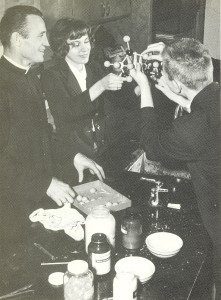 Fr. Eugene Lutz, CSV, works with students during a 1964 chemistry lab