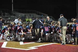 Fr. Dan Hall, center facing huddle, leads the team in prayer