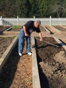 Associate Tim Schwarz spreads new soil across his bed
