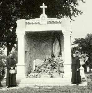 Br. John Koelzer, CSV, left, poses beside the shrine to Our Lady of Lourdes, after it was completed in 1918