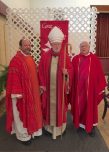 Fr. Dan Belanger, left, and Fr. James Fanale, right, assisted Abbot Hugh Anderson during the confirmation