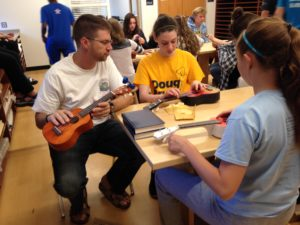 Br. John Eustice, CSV, helps a student with stringing her ukulele
