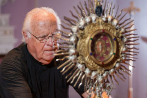 Fr. James Fanale, CSV, displays St. Anne relic. Daily Journal/John Dykstra