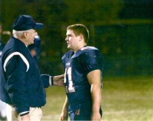 Fr. Dan Hall consoles a young Peter Lamick in 2006 after a loss in the high school playoffs
