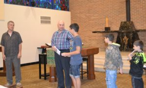 Marwan Saffaf introduces his three sons at the prayer service. Br. Michael Gosch, CSV, at left, looks on