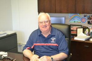 Fr. Mick Egan at his office at Saint Viator High School, surrounded by his Cubs memorabilia