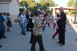 Fr. Bill Haesaert greets parishioners as they head to the Taste of St. Viator