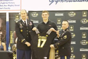 Capt. Johsua Frye, left and Staff Sgt. Christopher Spain, right, present Cole Kmet with his U.S. Army All-American Bowl jersey