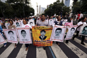 Relatives carry photos of some of the 43 missing students of the Ayotzinapa teachers' training college during a protest to mark the eleven-month anniversary of their disappearance in Mexico City
