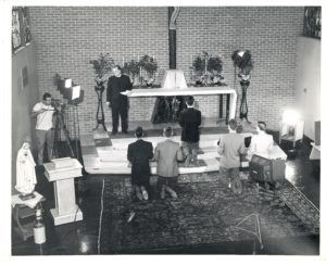 """Fr. Williams, at left in back, directs the """"Habit"""" scene in the chapel in the Viatorian Province Center"""
