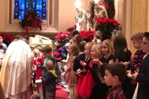 Fr. John Peeters, CSV, blesses each child's infant Jesus from their family creche